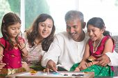 Happy Asian Indian family playing carrom game at home. Parents and children indoor lifestyle. poster