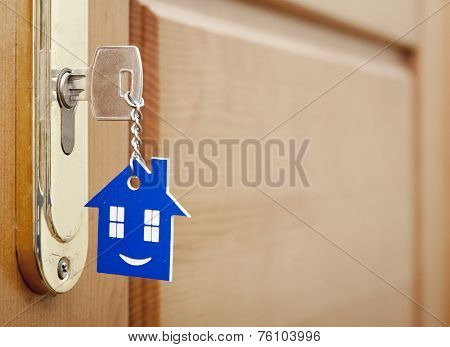 A key in a lock with house icon with smile on it