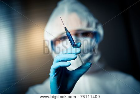 Researcher In Protective Suit Preparing A Syringe