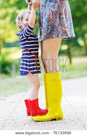 Young mother and little adorable child girl in rubber boots having fun together family look in summer park on sunny warm day. Long legs of woman. poster