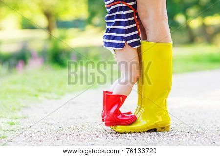 Legs Of Young Woman And Her Little Girl Daugher In Rainboots