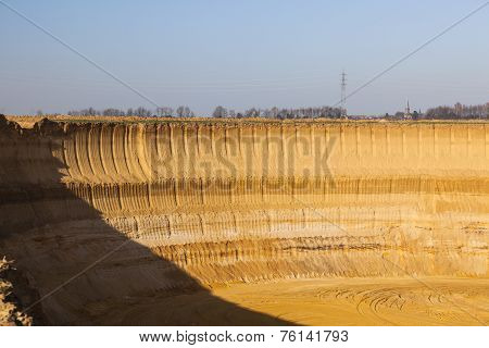 A steep lignite pit mine wall in warm evening light poster