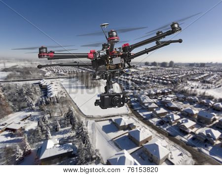 A drone with a camera and raised landing gears flying high above a residential area covered with fresh snow in a bright sunny winter day. poster