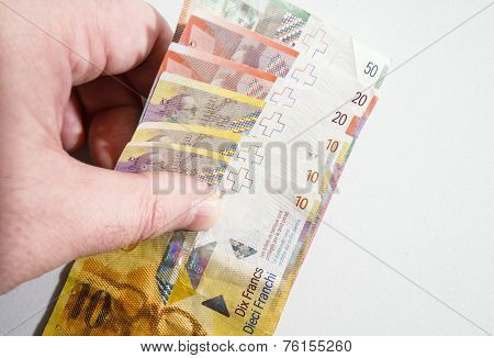 Hand Picking Up A Stack Of Swiss Franc Notes
