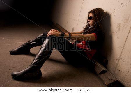 model pretty woman sitting against a wall gesturing