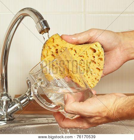 Hands wash the glass under running water in kitchen