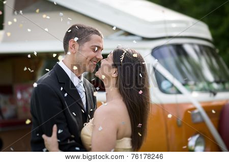 Happy Just Married Couple In A Classic Camper Van In A Field