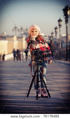Girl in a pink beret stand near the camera on a support