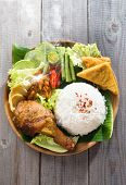 Popular Indonesian local food nasi ayam penyet, indonesian fried chicken rice with sambal belacan. Fresh hot with steam smoke. poster
