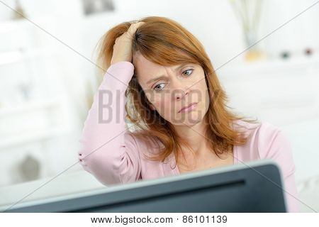 Stressed woman looking at her computer screen