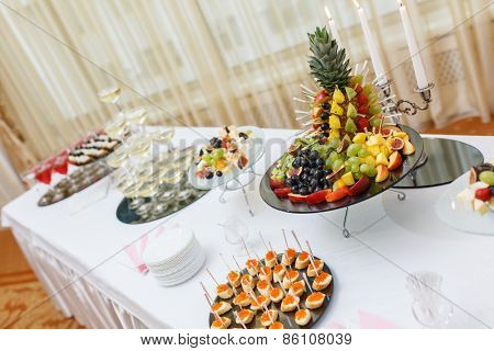 Table with cold snacks and tableware on luxury stand-up party