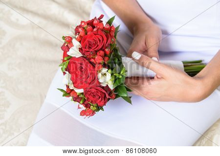 Beautiful red wedding bouquet of roses and freesia flowers in hands of the bride