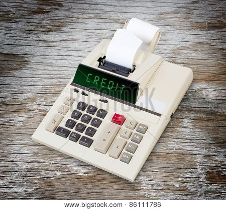 Old calculator showing a text on display - credit poster