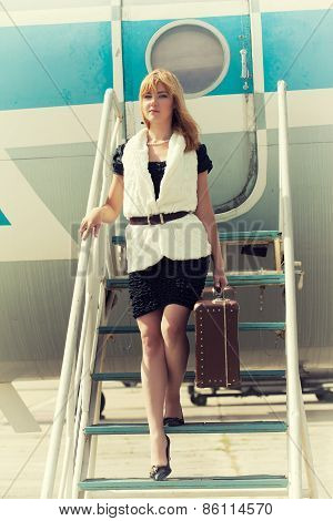 Beautiful Woman With Old Suitcase Posing On Plane Gangway