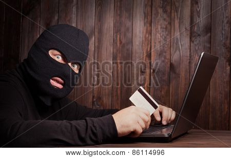 Hacker holding a credit card on wooden background poster