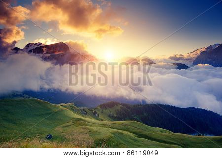 Great view of the foggy Val di Fassa valley with pass Sella. National Park. Dolomites (Dolomiti), South Tyrol. Location Canazei, Campitello, Mazzin. Italy, Europe. Dramatic scene. Beauty world.