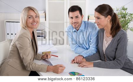 Professional business meeting: young couple as customers and an adviser for finance, investment or insurance. poster