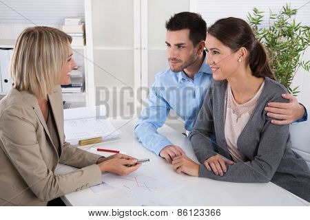 Professional business meeting: young couple as customers and an adviser for finance, investment or insurance.