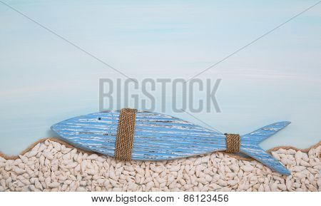 Blue wooden fish on turquoise background with shells. Christian symbol.