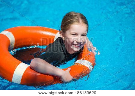 happy little girl swims in a wetsuit with a lifeline in the pool