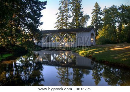 White Covered Bridge Reflected In Water