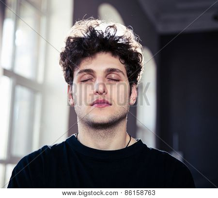 Portrait of a young handsome man with closed eyes