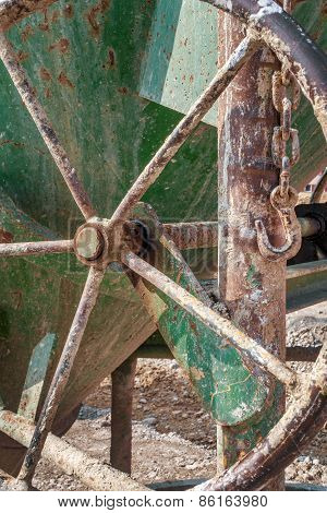 Handwheel on an old green concrete bucket
