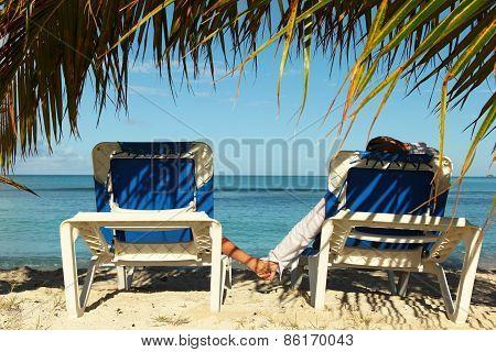 Couple On The Sun Lounges Enjoying Holidays