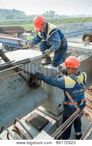 Two workers busy on bridge construction
