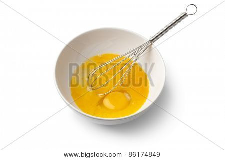 Beaten egg yolks in a bowl with whisk on white background