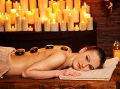 Young woman having Ayurveda stone massage. Many candles in background. poster