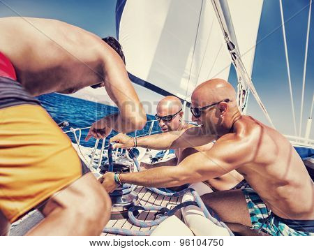 Group of handsome shirtless sailors working on sailboat, involved in maritime competition, enjoying water sport, active summer vacation