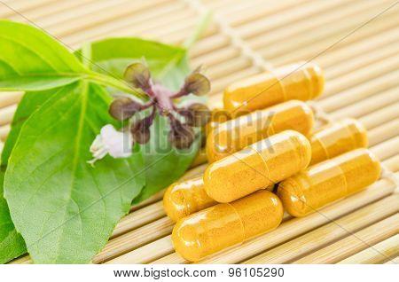 Alternative Medicine Tablets On A Wooden Mat.