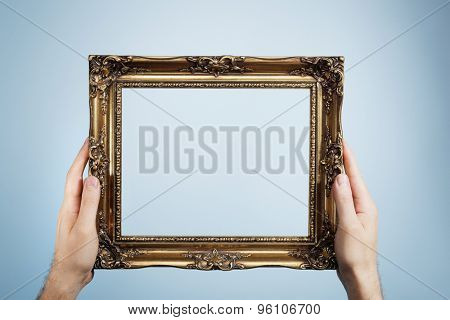 Man holding an antique look golden picture frame in his hands.