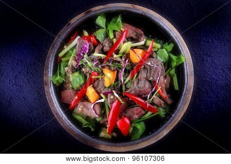 Thai Food - Stir fried Pork liver with goat pepper, sweet pepper, scallion and celery on hot plate