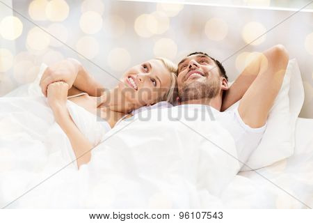 people, family, bedtime and happiness concept - happy couple lying in bed at home over lights background