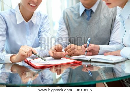 Image of business people sharing ideas round the table at meeting poster
