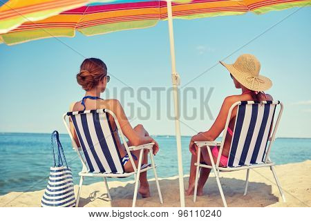 summer vacation, travel and people concept - happy women sunbathing in lounges on beach