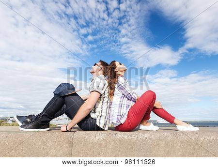 summer holidays and teenage concept - teenagers sitting back to back and looking up in the sky
