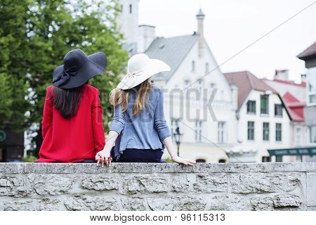 Girls Hold Hands Sitting On The Fence