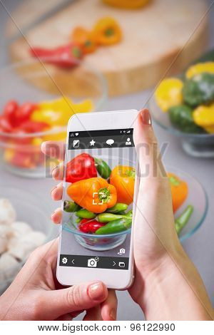 Hand holding smartphone against close up of pimentos