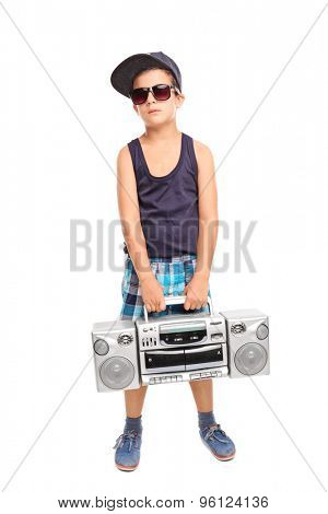 Full length portrait of a cool kid in hip-hop clothes holding a radio and looking at the camera isolated on white background