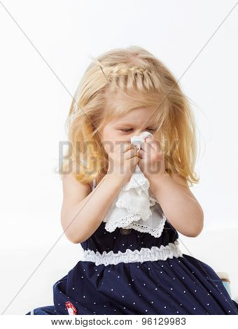 Little girl wiping her nose with handkerchief