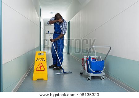 Tired Janitor Cleaning Floor