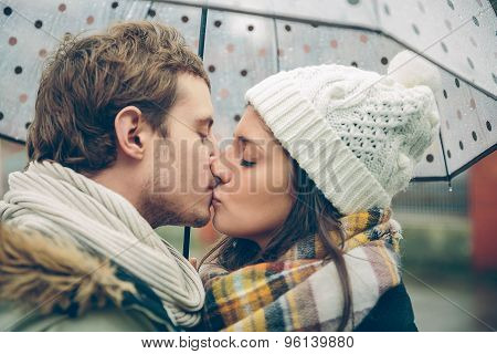 Young couple kissing outdoors under umbrella in a rainy day