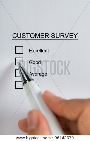 Close-up Of Person Hands Filling Customer Survey Form With Pen poster