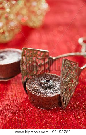 Chocolate Cherry Mini Tartlets in vintage tongs  with festive golden red style, shallow dof