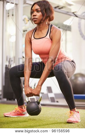 Woman exercising in a gym with a kettlebell weight, vertical