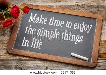 Make time to enjoy the simple things  inspirational advice - white chalk text on a vintage slate blackboard with red roses against rustic wood