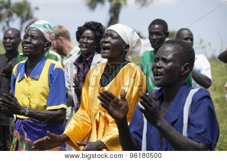 PANWEL, SOUTH SUDAN-NOVEMBER 2, 2013: Unidentified worshippers sing and clap at an outdoor worship service in South Sudan